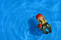 Doll on blue water floating in a swimming pool Royalty Free Stock Photo