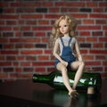 Doll with a bottle the concept of alcoholism beautiful Royalty Free Stock Photography