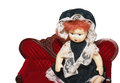 Doll on red sofa