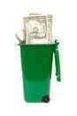 Dollar banknotes in green wheelie bin