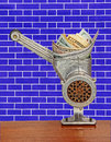 Dollar banknotes in meat grinder on blue brick wall background.M Royalty Free Stock Photo
