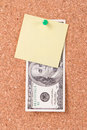 Dollar bill and sticky post on cork board one hundred blank empty yellow affixed to with green pin Royalty Free Stock Photo