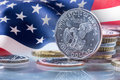 Dollar coins and USA flag in the background. USA Dollar coins standing on edge supported on coins Royalty Free Stock Photo