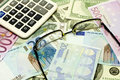 Dollar, euro banknotes, calculator and glasses Royalty Free Stock Photography