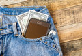 Dollar money and smart phone in pocket blue jeans on wooden background Royalty Free Stock Photo