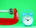 Dollar under pressure a silver symbol placed in a red clamp with a pastel green background with a light blue alarm clock in the Royalty Free Stock Photos