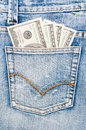 Dollars in the back pocket american hundred dollar bills of blue jeans pants Stock Photo