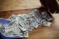 Dollars and broom on wooden floor