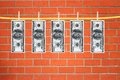 Dollars laundering and dry after wash hang on clothespins over orange brick wall Royalty Free Stock Photo