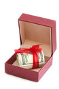 Dollars laying in red decorated gift box isolated on a white Stock Photos