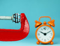 Dollars tmely crush a silver dollar symbol placed in a red clamp with a pastel blue background with an orange alarm clock in the Royalty Free Stock Photo
