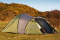 Dome tent pitched in field for wild camping in the great outdoors with front flap open showing interior Stock Photo