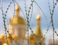 The domes of the orthodox cathedral photographed behind barbed wire at background blue sky Royalty Free Stock Photos