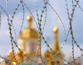 The domes of the orthodox cathedral photographed behind barbed wire at background blue sky Stock Photos
