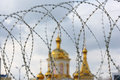 The domes of the orthodox cathedral photographed behind barbed wire at background blue sky Royalty Free Stock Photography