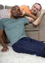Domestic gay couple two lovers relaxing at home in the livingroom Royalty Free Stock Photography