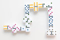 Domino effect shot. Look down for domino game. Dominoes falling in a row in front. Dominoes Game Pieces Isolated on Royalty Free Stock Photo