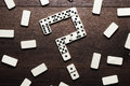 Domino pieces forming question mark over wooden table Stock Photo