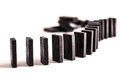 Dominoes in a line black curved ready to topple on white background Stock Photography
