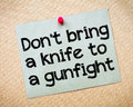 Don t bring a knife to a gunfight message recycled paper note pinned on cork board concept image Royalty Free Stock Image