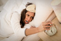 Don t want to wake up beautiful young woman frowning in bed and holding hand on alarm clock she is doesn Royalty Free Stock Photo