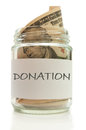 Donation glass jar filled with banknotes labeled with Royalty Free Stock Photography