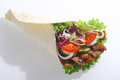 Doner with grilled meat and fresh salad filling or corn taco wrap filled including lettuce tomato onion cucumber on a white Stock Photos