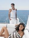 Donna che si trova sull yacht di sofa with man standing in Immagine Stock Libera da Diritti