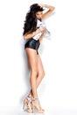 Donna con le gambe sexy lunghe che portano i bicchierini ed il rivestimento di cuoio del denim su fondo bianco Fotografia Stock