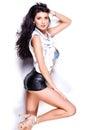 Donna con le gambe sexy lunghe che portano i bicchierini ed il rivestimento di cuoio del denim su fondo bianco Fotografie Stock