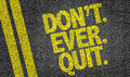 Dont ever quit written on the road Royalty Free Stock Photo