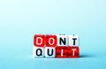 Dont quit do it written on red and white dices on blue background Royalty Free Stock Images
