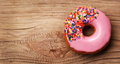 Donut with sprinkles on wooden background Royalty Free Stock Photo