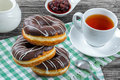 Donuts with Chocolate Icing, a cup of tea, close-up Royalty Free Stock Photo