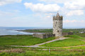 Doonagore castle irish stone guardian between green fields and sea ireland Royalty Free Stock Photo