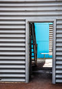 Through the door blue accent wall a metal building exterior with entryway open looking towards a sky with bench and stairs Royalty Free Stock Images