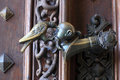 Door handle with raven killing a man in palace Stock Photos