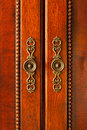 Door handles on cabinet ornate wooden doors closeup Royalty Free Stock Photo