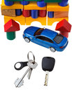 Door keys vehicle key new blue car model close up and wooden block toy house isolated on white background Royalty Free Stock Image
