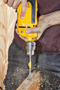 Door knob installing using  yellow power drill, sawdust flying a Royalty Free Stock Photo