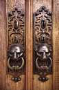 Door knobs two with knocking rings and animal heads in wooden doors Royalty Free Stock Image