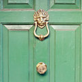 Door knocker brass lion head on a green front Stock Photos