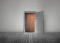 Door open to reveal red brick wall blocking the way in a dull grey room Royalty Free Stock Image