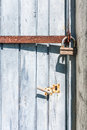 Door padlocked old wooden closed with an iron bar and a padlock Stock Photos