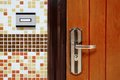 Doorbell ring button on the wall and metal door fragment with handle close up Stock Photography