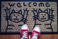 Doormat and a pair of sneakers Royalty Free Stock Photography