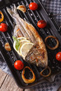 Dorado fish with vegetables closeup on the grill pan. Vertical t Royalty Free Stock Photo