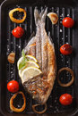 Dorado fish with vegetables closeup on the grill. Vertical top v Royalty Free Stock Photo