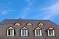 Dormer windows in a row with blue sky Stock Image
