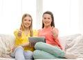 Dos adolescentes sonrientes con pc de la tableta en casa Imagen de archivo libre de regalías